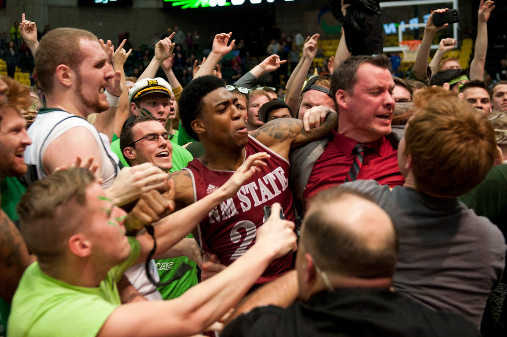 . In this Thursday, Feb. 27, 2014 photo, New Mexico State\'s Daniel Mullings, center left in red and white jersey, is involved in a brawl involving players and fans who came onto the court when New Mexico State guard K.C. Ross-Miller hurled the ball at Utah Valley\'s Holton Hunsaker seconds after the Wolverines\' 66-61 overtime victory against the Aggies.  (AP Photo/The Daily Herald, Grant Hindsley)