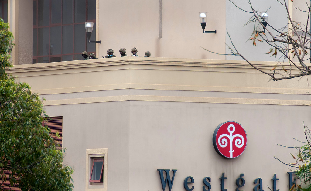 . Kenyan soldiers are seen on an upper floor balcony of the Westgate Mall following large explosions and heavy gunfire, in Nairobi, Kenya Monday, Sept. 23, 2013. F. (AP Photo/Jonathan Kalan)