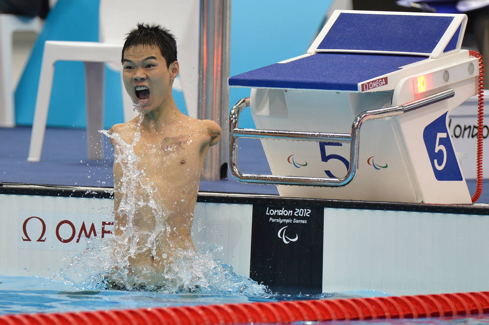 Description of . China's Zheng Tao celebrates breaking the world record after winning the men's 100m backstroke - S6 swimming event during the London 2012 Paralympic Games at the Olympic Park Aquatics Centre in east London on August 30, 2012.  AFP PHOTO / BEN  STANSALL/AFP/Getty Images
