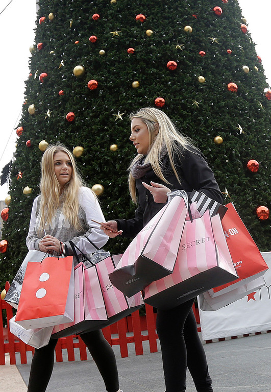 . Maggie, left, and her friend Maddy, last names not given, carry shopping bags after having their photo taken in front of a large tree at Union Square in San Francisco, Friday, Nov. 25, 2016. Black Friday, historically the starting line of the retail industry\'s crucial holiday buying season, isn\'t quite the one-day spree it used to be. Some retailers have pushed their biggest Black Friday door-buster deals into Thanksgiving Day and spread other promotions to even earlier in the season. (AP Photo/Jeff Chiu)