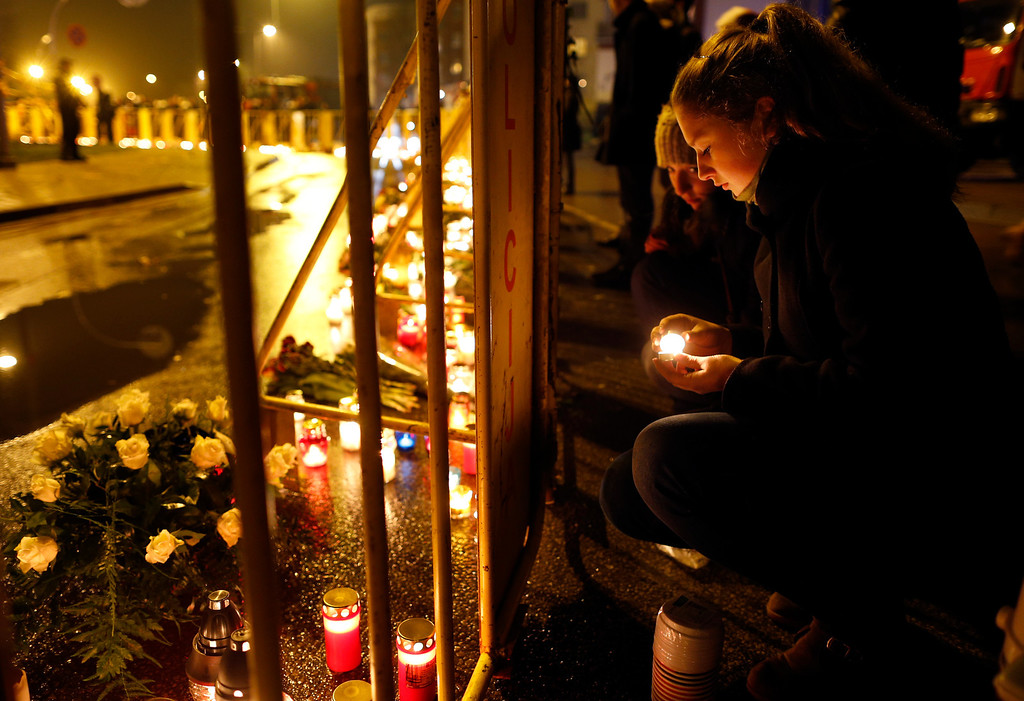 . A woman lights a candle near the collapsed shopping centre in  Riga, Latvia, Friday, Nov. 22, 2013.  (AP Photo/Mindaugas Kulbis)