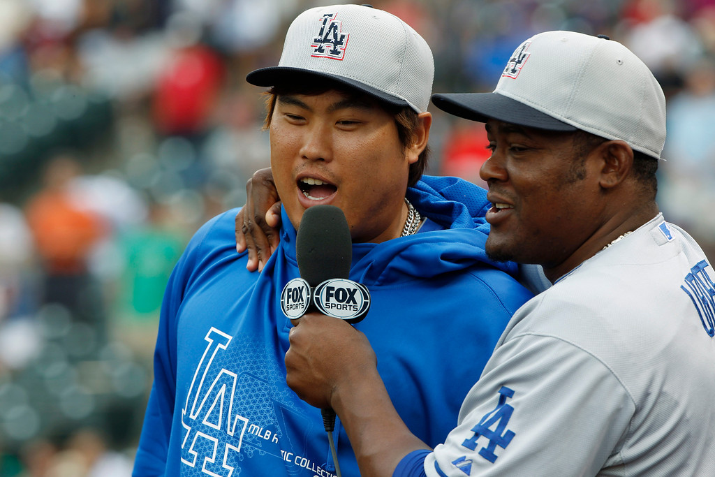. Los Angeles Dodgers pitcher Hyun-Jin Ryu, left, is interviewed by infielder Juan Uribe as part of a joke before the Dodgers face the Colorado Rockies in the first inning of a baseball game in Denver, Thursday, July 4, 2013. (AP Photo/David Zalubowski)
