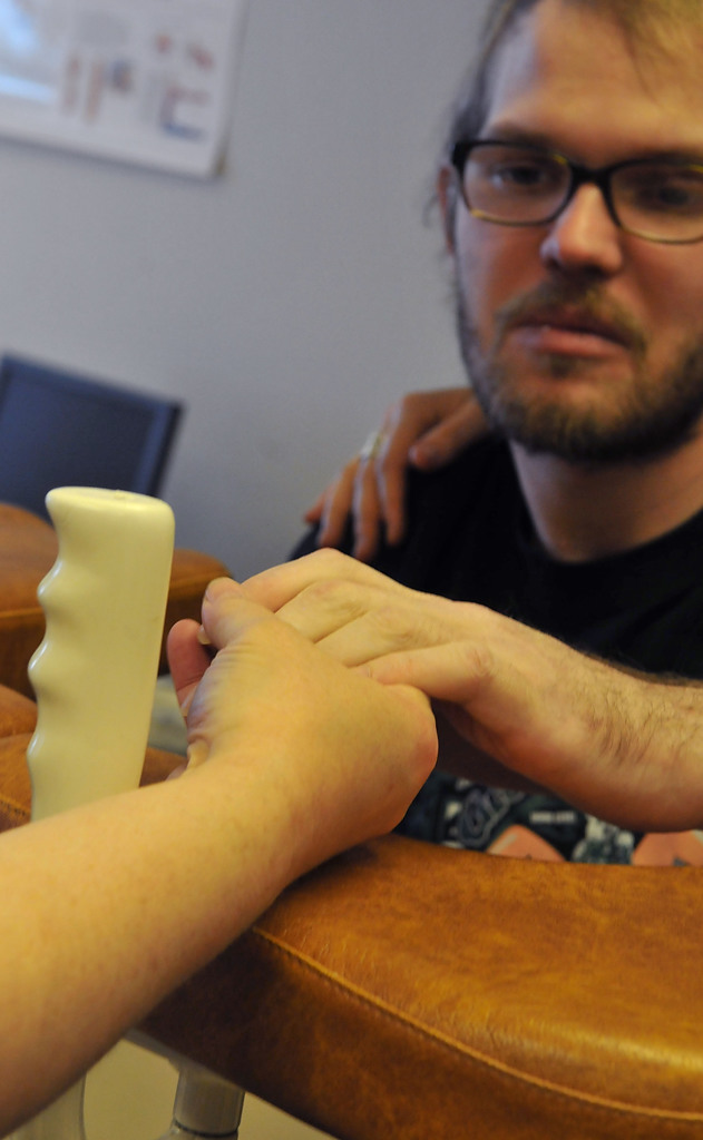 . Chreryl Young, mom of Zack Mohs, gives motherly love as she holds his hand during physical therapy. (Pioneer Press: John Doman)