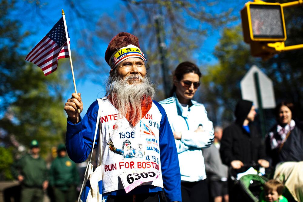 Description of . A participant wearing a singlet in tribute to victims of the Boston Marathon bombing, walks holding a miniature U.S. flag after a race organized by the New York Road Runners at Central Park in New York April 21, 2013. The New York Police Department has tightened security during the race in response to the bomb attacks at Boston Marathon, according to local media. REUTERS/Eduardo Munoz
