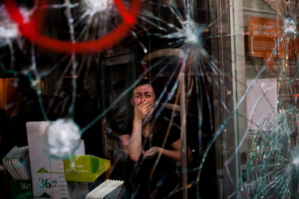 . In this March 29, 2012 file photo, Mireia Arnau, 39, reacts behind the broken glass of her shop stormed by demonstrators during clashes at the general strike in Barcelona. Spanish workers livid over labor reforms they see as flagrantly pro-business staged a nationwide strike and tried to bring the country to a halt by blocking traffic, closing factories and clashing with police in rowdy demonstrations. (AP Photo/Emilio Morenatti, File)