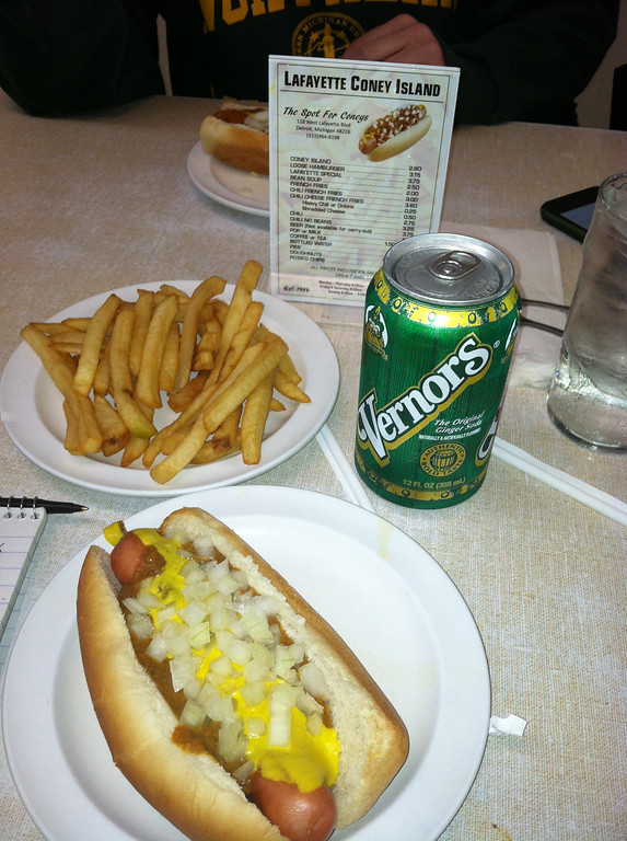 . This Dec. 2, 2014 photo shows a Coney Island hot dog at Lafayette Coney Island with an order of fries and Vernors, a ginger ale that originated in Detroit. Coney-style hot dogs are a tradition in Michigan, served with onions, mustard and chili. Lafayette is located next to American Coney Island, a rival eatery in downtown Detroit. The two restaurants were founded by brothers who were Greek immigrants in the early 20th century and many locals swear allegiance to one or the other. (AP Photo/Beth J. Harpaz)