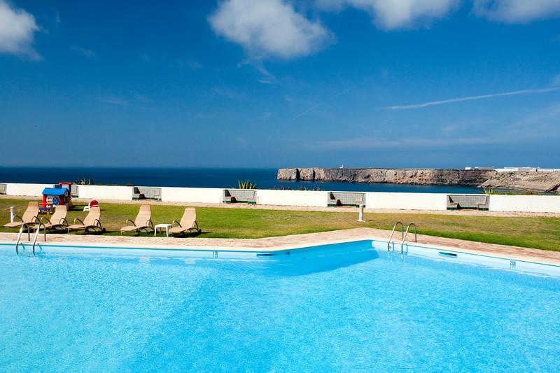 Swimming pool of Pousada Infante de Sagres Hotel with Sagres point on the background. Town of Sagres, municipality of Vila do Bispo, district of Faro, region of Algarve, southwestern Portugal