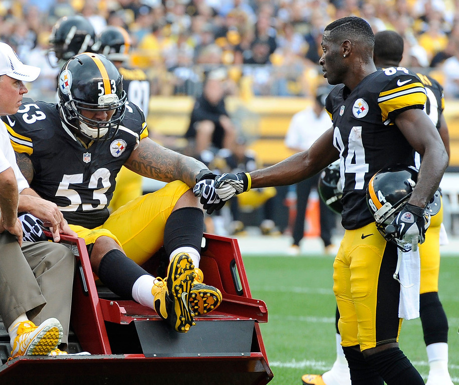 . Pittsburgh Steelers center Maurkice Pouncey (53), is acknowledged by wide receiver Antonio Brown (84) as he is taken from the field after being injured in the first quarter an NFL football game against the Tennessee Titans, Sunday, Sept. 8, 2013, in Pittsburgh. (AP Photo/Don Wright)