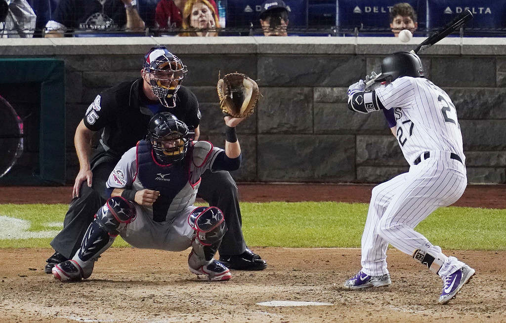 . Colorado Rockies Trevor Story (27) tries to avoid a wild pitch in the ninth inning during the Major League Baseball All-star Game, Tuesday, July 17, 2018 in Washington.(AP Photo/Carolyn Kaster)