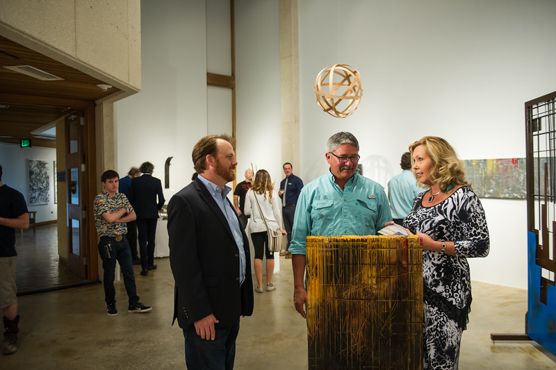 Artist Pual seeman chats with a couple that came to observe the works of art