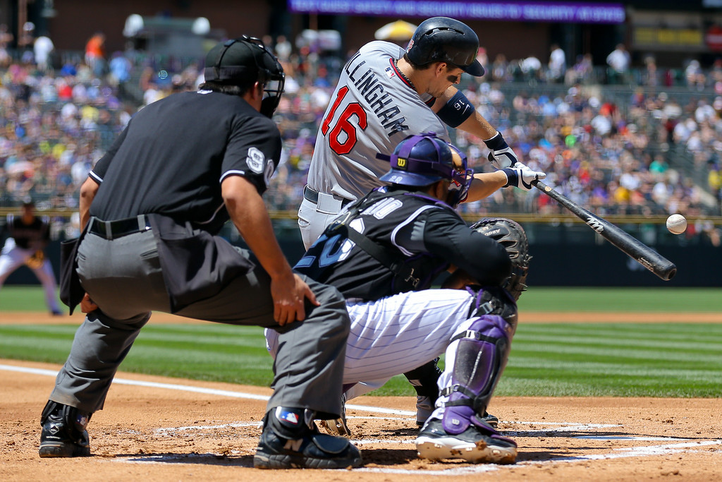 . Josh Willingham #16 of the Minnesota Twins hits a single during the first inning as catcher Wilin Rosario #20 of the Colorado Rockies and home plate umpire Mark Ripperger look on. (Photo by Justin Edmonds/Getty Images)