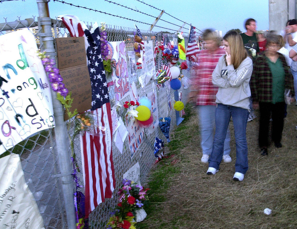 . Mourners visit a makeshift memorial, Sunday, Feb. 2, 2003, outside the Johnson Space Center in Houston honoring the seven astronauts who perished aboard the Space Shuttle Columbia on Saturday. (AP Photo/Matt York)