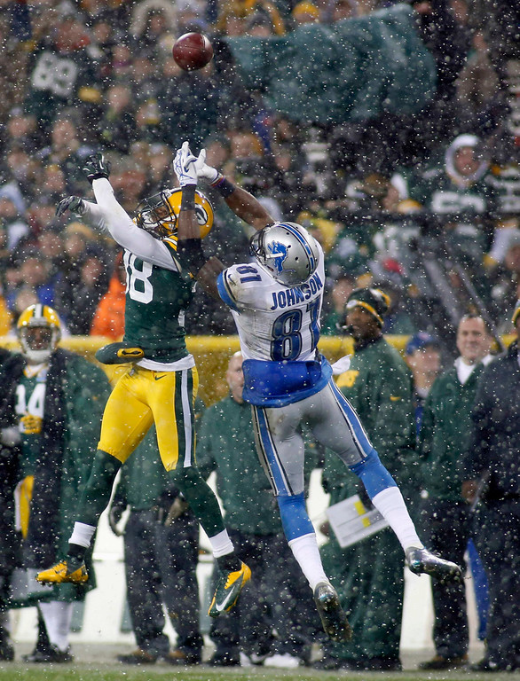 . Green Bay Packers cornerback Tramon Williams (L) and Detroit Lions wide receiver Calvin Johnson go up for a pass during the first half of a NFL football game in Green Bay, Wisconsin December 9, 2012. REUTERS/Darren Hauck