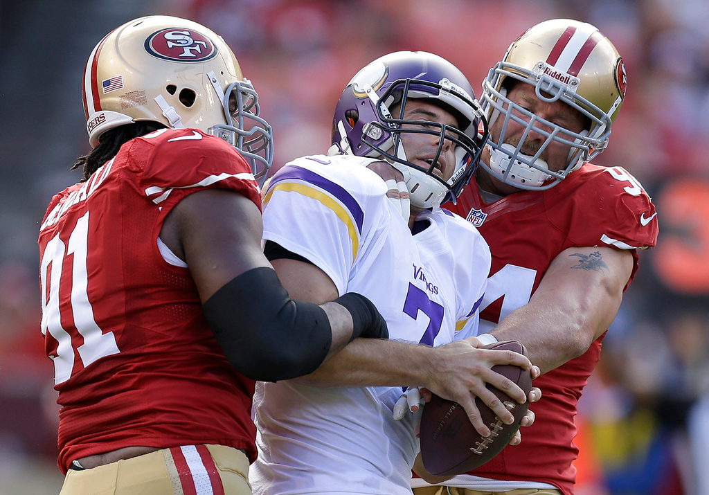. Vikings quarterback Christian Ponder is grabbed by 49ers defensive tackle Ray McDonald, left and defensive tackle Justin Smith after the play was stopped for a time out during the first quarter. (AP Photo/Ben Margot)