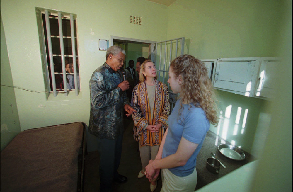 Description of . South African President Nelson Mandela, left, escorts United States first lady Hillary Rodham Clinton and her daughter Chelsea, foreground Thursday, March 20, 1997 through the cell on Robben Island where he stayed for 18 of his 27 years of imprisonment. (AP Photo/Doug Mills)