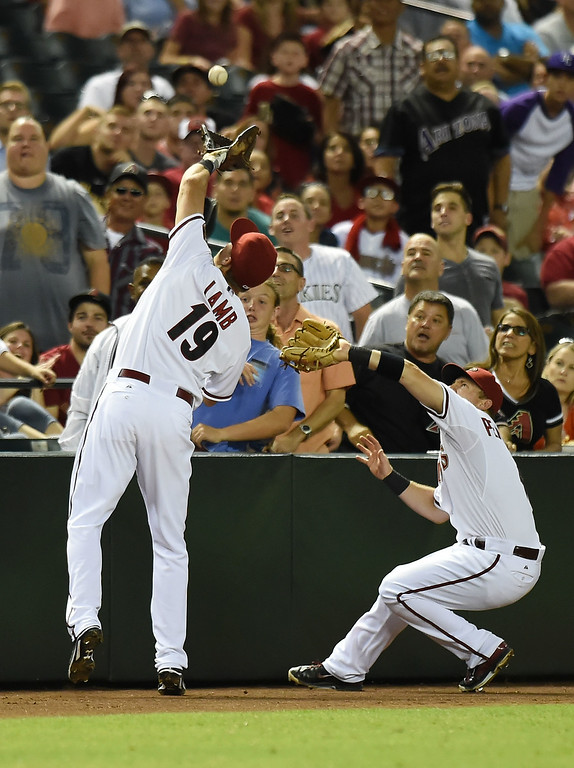 . Jake Lamb #19 of the Arizona Diamondbacks makes a catch in foul territory just in front of teammate Cliff Pennington #4 during the sixth against the Colorado Rockies at Chase Field on August 8, 2014 in Phoenix, Arizona.  (Photo by Norm Hall/Getty Images)
