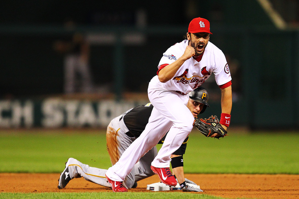 . Matt Carpenter #13 of the St. Louis Cardinals celebrates making a double play on a ball hit by Starling Marte #6 as Clint Barmes #12 of the Pittsburgh Pirates reacts in the sixth inning of Game Five of the National League Division Series at Busch Stadium on October 9, 2013 in St Louis, Missouri.  (Photo by Dilip Vishwanat/Getty Images)