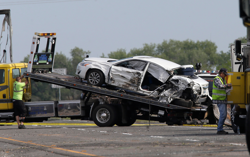 Description of . A passenger car involved in a multi-vehicle accident that left at least ten people dead and dozens injured, sits on tow truck on Interstate 5, Friday, April 11, 2014 in Orland, Calf.   A FedEx truck traveling on southbound Interstate 5, Thursday, veered across a grassy highway median and slammed into the bus that was carrying 40 high school students  on a visit to a Northern California College.  (AP Photo/Rich Pedroncelli)