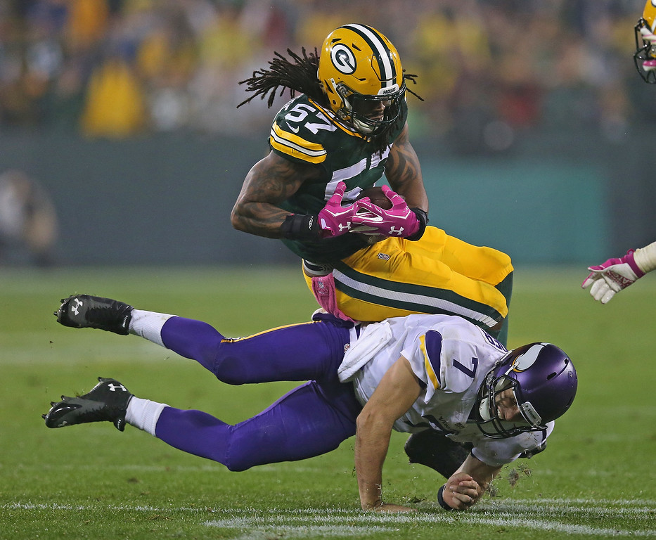 . GREEN BAY, WI - OCTOBER 02:  Christian Ponder #7 of the Minnesota Vikings tackles Jamari Lattimore #57 of the Green Bay Packers after an interception at Lambeau Field on October 2, 2014 in Green Bay, Wisconsin.  (Photo by Jonathan Daniel/Getty Images)