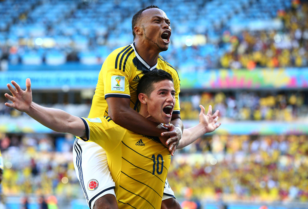 . James Rodriguez of Colombia celebrates scoring his teams third goal with Juan Camilo Zuniga during the 2014 FIFA World Cup Brazil Group C match between Colombia and Greece at Estadio Mineirao on June 14, 2014 in Belo Horizonte, Brazil.  (Photo by Ian Walton/Getty Images)