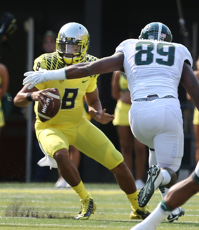 . Oregon quarterback Marcus Mariota, left, is flushed out of the pocket by Michigan State\'s Shilique Calhoun during the first quarter of their college football game in Eugene, Oregon, Saturday Sept. 6, 2014. (AP Photo/Chris Pietsch)