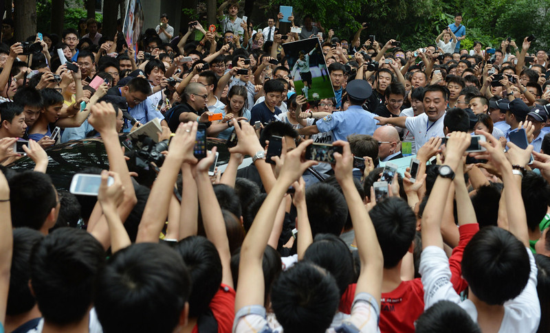 """. A huge crowd gathers around the car (centre L) carrying football superstar David Beckham at Tonji University in Shanghai on June 20, 2013.  Football superstar David Beckham\'s visit to China turned \""""chaotic\"""" on Thursday after at least five people were hurt in a stampede as fans rushed to see him, local media and an AFP photographer at the scene said.  PETER PARKS/AFP/Getty Images"""