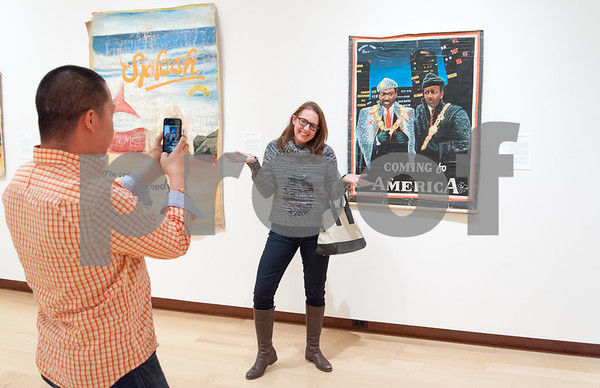 02/02/18 Wesley Bunnell | Staff Kate Farrar, who has never seen the movie Coming to America, poses next to a hand painted poster of the movie as her photo is taken by Chan Lieu on Friday Friday Feb 2. The poster is part of a collection of Ghanian Movie Posters primary from the 1980's through the 1990's showing Hollywood movies in the African country.