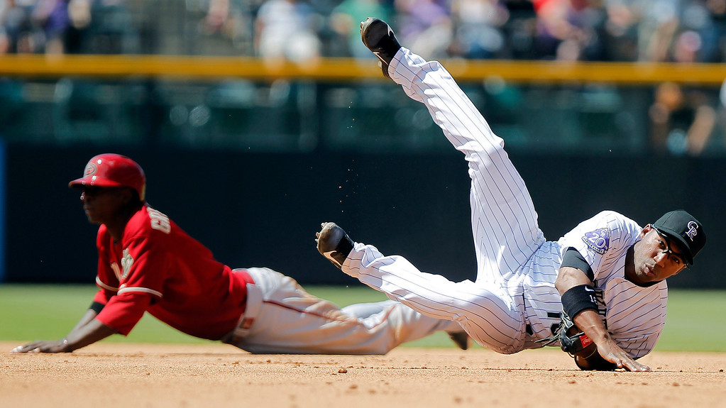 . Arizona Diamondbacks\' Didi Gregorius, rear left, is out at second as Colorado Rockies\' Jonathan Herrera tumbles after throwing out Arizona Diamondbacks\' Paul Goldschmidt at first for the double play during the fifth inning of a baseball game Wednesday, May 22, 2013 in Denver. The Rockies won 4-1. (AP Photo/Barry Gutierrez)