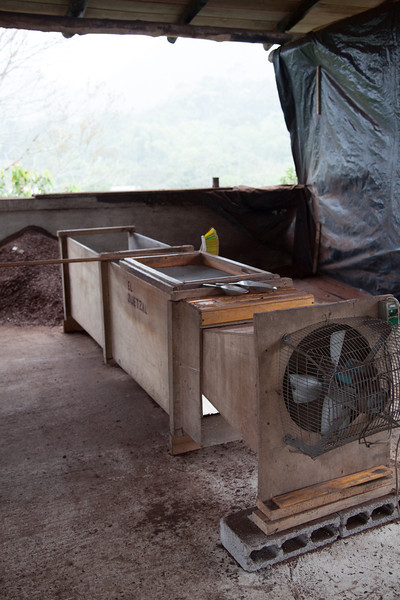 The apparatus used to take the shell/husk off of the cocoa beans - beans are agitated across a wire mesh on top, and the fan blows the husks away while the beans drop to the bottom.