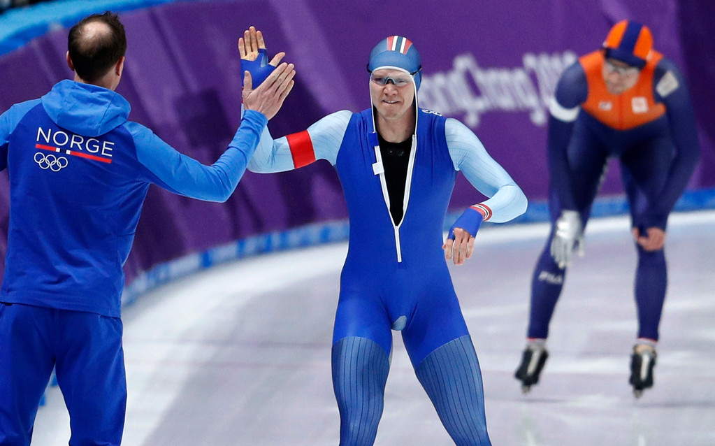 . Gold medalist and new Olympic record holder Havard Lorentzen of Norway celebrates with his coach after defeating Ronald Mulder of The Netherlands, rear, during the men\'s 500 meters speedskating race at the Gangneung Oval at the 2018 Winter Olympics in Gangneung, South Korea, Monday, Feb. 19, 2018. (AP Photo/John Locher)