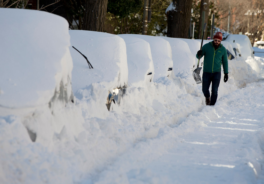. Ben Osborn walks with a shovel past a line of snowed-in cars A Steet in northeast Washington, Sunday, Jan. 24, 2016. Washington is digging out after a mammoth blizzard with hurricane-force winds and record-setting snowfall brought much of the East Coast to an icy standstill. (AP Photo/Carolyn Kaster)