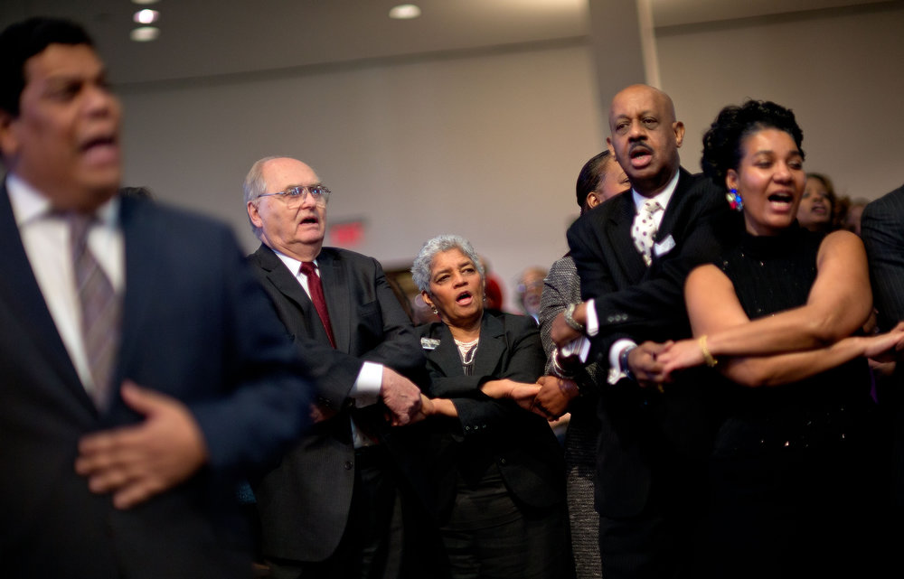 Description of . Shirley Franklin, center, former mayor of Atlanta, joins hands with Walt Bryde, left, and Jeremiah Bridgewater, right, during the singing of 'We Shall Overcome' to conclude the Dr. Martin Luther King Jr. holiday commemorative service at the Ebenezer Baptist Church, Monday, Jan. 21, 2013, in Atlanta. The nation will honor civil rights leader Martin Luther King Jr. on Monday, the same day as it celebrates the inauguration of the first black president to his second term. (AP Photo/David Goldman)