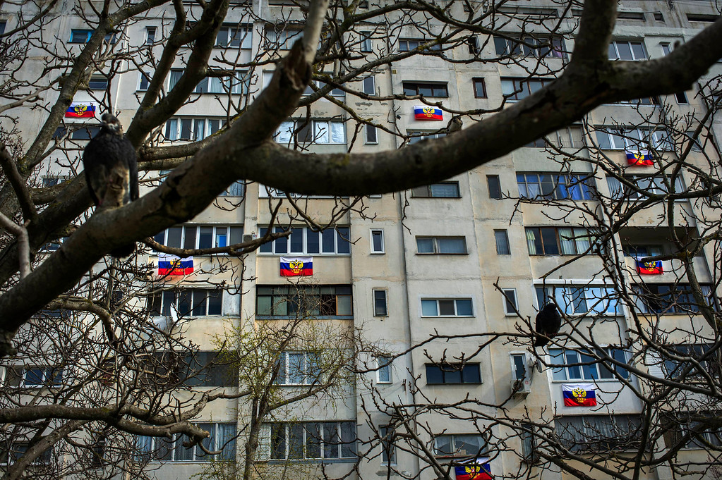 . Russian flags are hung out on an apartment building in a residential district in Sevastopol, Ukraine, Friday, March 14, 2014. Crimea plans to hold a referendum on upcoming Sunday that will ask residents if they want the territory to become part of Russia. Ukraine\'s government and Western nations have denounced the referendum as illegitimate and warned Russia against trying to annex Crimea. (AP Photo/Andrew Lubimov)