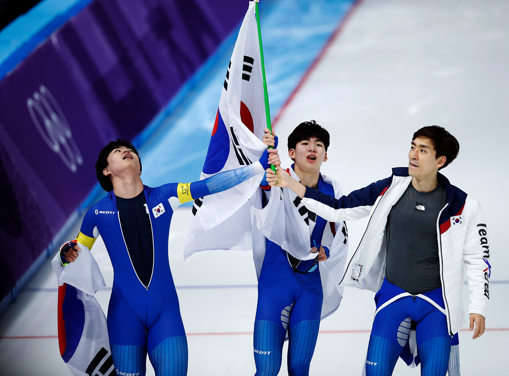 . Silver medalist team Korea with Lee Seung-hoon, right, Chung Jaewon, center, Kim Min-seok,right, celebrates with the national flag after the men\'s team pursuit speedskating race at the Gangneung Oval at the 2018 Winter Olympics in Gangneung, South Korea, Wednesday, Feb. 21, 2018. (AP Photo/Vadim Ghirda)