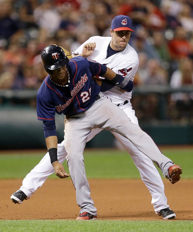 . Indians third baseman Lonnie Chisenhall, right, tags out Minnesota\'s Pedro Florimon, who was caught in a rundown while trying to steal third base  in the seventh inning. (AP Photo/Tony Dejak)