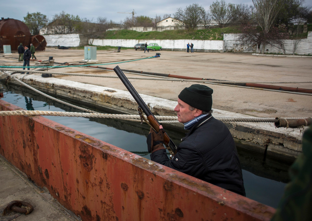 . A pro-Russian forces member keeps watch during the seizure of the Ukrainian corvette Pridniprovya in Sevastopol, Crimea, Thursday, March 20, 2014.  (AP Photo/Andrew Lubimov)