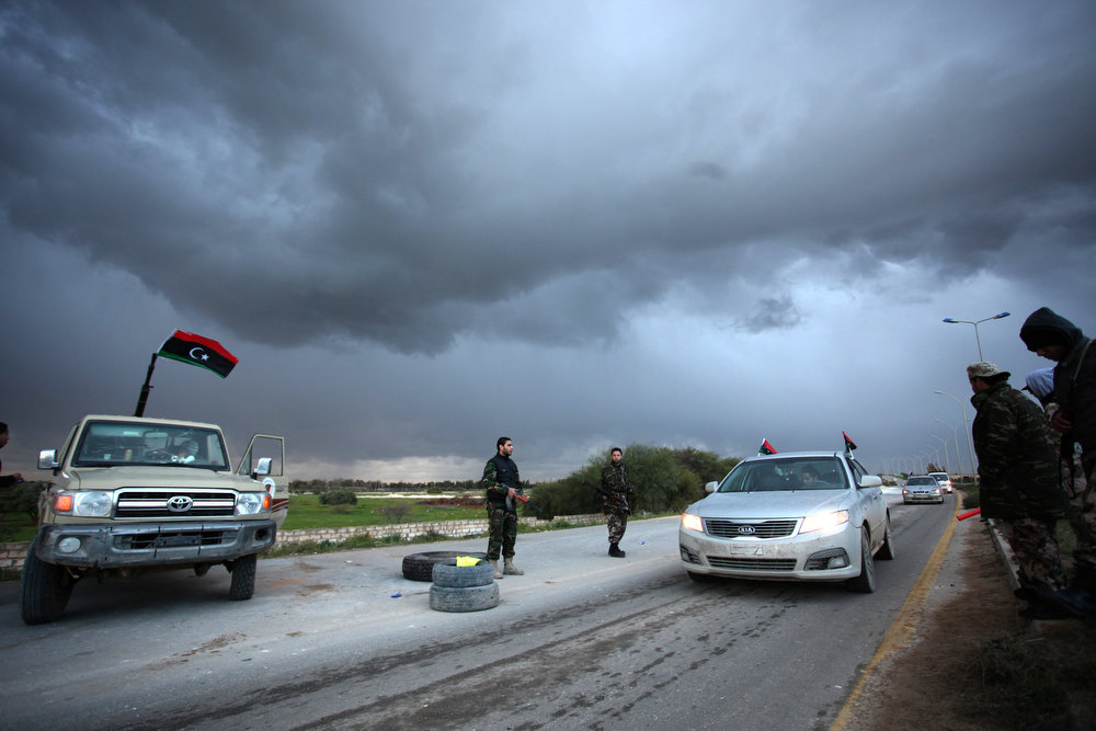 Description of . Libyan security forces check the cars on the side of the highway leading to downtown Benghazi, Libya, Friday, Feb. 15, 2013. Libyans are preparing to mark the second anniversary of the uprising that ousted Moammar Gadhafi.  (AP Photo/Mohammad Hannon)