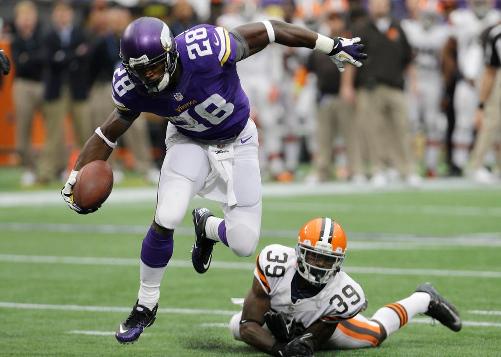 . Vikings running back Adrian Peterson  runs from  Browns free safety Tashaun Gipson during a 2-yard touchdown run in the first quarter. (AP Photo/Ann Heisenfelt)