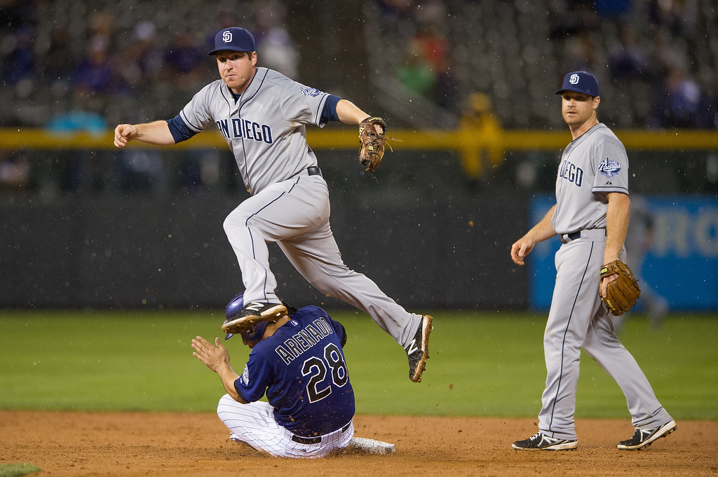 . Jedd Gyorko #9 of the San Diego Padres throws to first base after an error in the seventh inning as Nolan Arenado #28 of the Colorado Rockies slides safely into second base and Logan Forsythe #11 looks on at Coors Field on August 12, 2013 in Denver, Colorado. A rain delay was called in the eighth inning with the Rockies leading 8-1.  (Photo by Dustin Bradford/Getty Images)