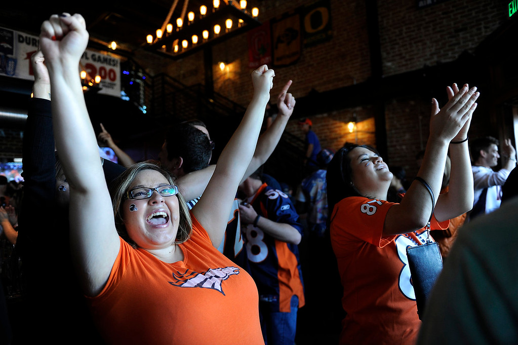 . Alex Santistevan throws her hands in the air in celebration after a Broncos touchdown during an AFC Championship watch party at the View House in Denver, Colorado on January 19, 2014. Broncos fans cheered on their team from sports bars around the city on Sunday. (Photo by Seth McConnell/The Denver Post)
