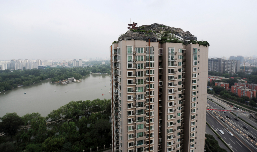 . This Aug. 12, 2013 photo released by China\'s Xinhua News Agency shows a residential building with a rocky style villa on its roof, in Haidian District of Beijing, China. Beijing authorities are planning to demolish a bizarre rooftop villa embedded in rocks, trees and bushes that allegedly was built illegally atop a 26-story apartment block in the capital. (AP Photo/Xinhua, Luo Xiaoguang)