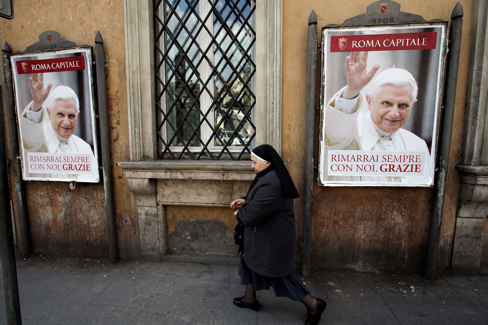 ". A nun walks past posters of Pope Benedict XVI reading in Italian, "" You will stay always with us. Thank you\"" along a street in Rome, Thursday, Feb. 28, 2013. Shortly before 5 p.m. on Thursday, Benedict will leave the Apostolic palace inside the Vatican for the last time as pontiff, head to the helipad at the top of the hill in the Vatican gardens and fly to the papal retreat at Castel Gandolfo south of Rome. There, at 8 p.m. sharp, Benedict will become the first pontiff in 600 years to resign. (AP Photo/Gregorio Borgia)"
