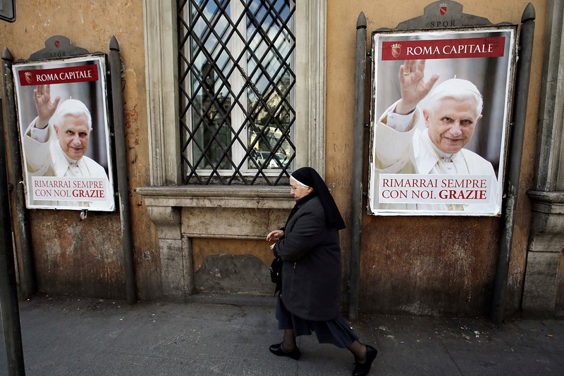 """. A nun walks past posters of Pope Benedict XVI reading in Italian, \"""" You will stay always with us. Thank you\"""" along a street in Rome, Thursday, Feb. 28, 2013. Shortly before 5 p.m. on Thursday, Benedict will leave the Apostolic palace inside the Vatican for the last time as pontiff, head to the helipad at the top of the hill in the Vatican gardens and fly to the papal retreat at Castel Gandolfo south of Rome. There, at 8 p.m. sharp, Benedict will become the first pontiff in 600 years to resign. (AP Photo/Gregorio Borgia)"""