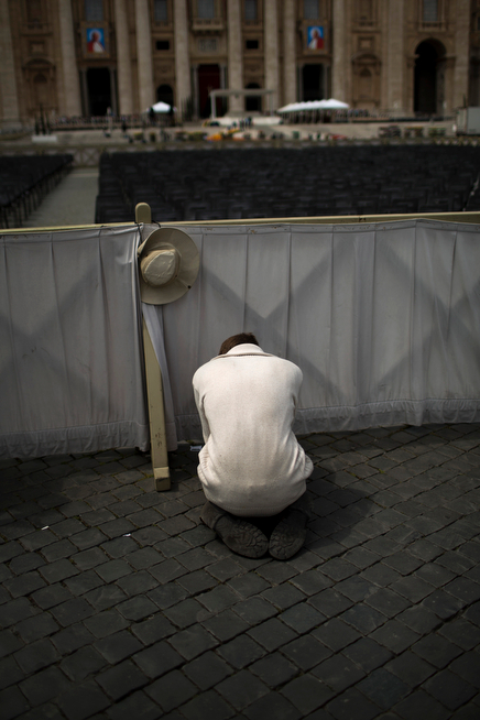 . A worshiper prays in St. Peter\'s Square at the Vatican, Saturday, April 26, 2014. Pilgrims and faithful are gathering in Rome to attend Sunday\'s ceremony at the Vatican where Pope Francis will elevate in a solemn ceremony John XXIII and John Paul II to sainthood. (AP Photo/Emilio Morenatti)