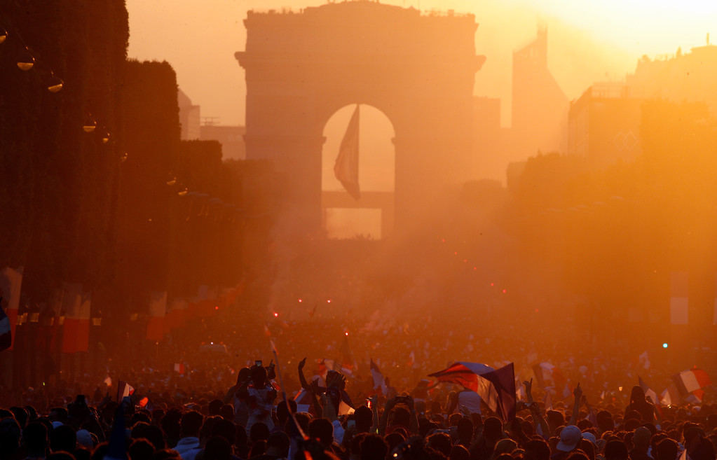 . A crowd invades at sunset the Champs Elysees avenue, with the Arc de Triomphe in background, after France won the soccer World Cup final match between France and Croatia, Sunday, July 15, 2018 in Paris. France won its second World Cup title by beating Croatia 4-2 . (AP Photo/Francois Mori)