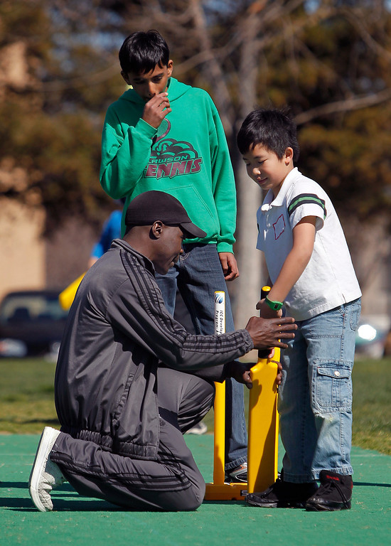 . At left, cricket coach Owen Graham teaches Tedrick Tang, 8, how to properly grip the bat at the cricket festival sponsored by the California Cricket Academy at the Cupertino Library Field\'s cricket pitch in Cupertino, Calif. on Saturday, March 9, 2013.  Boys and girls ages 5-13 were invited to attend and learn the basics of the game.  (LiPo Ching/Staff)