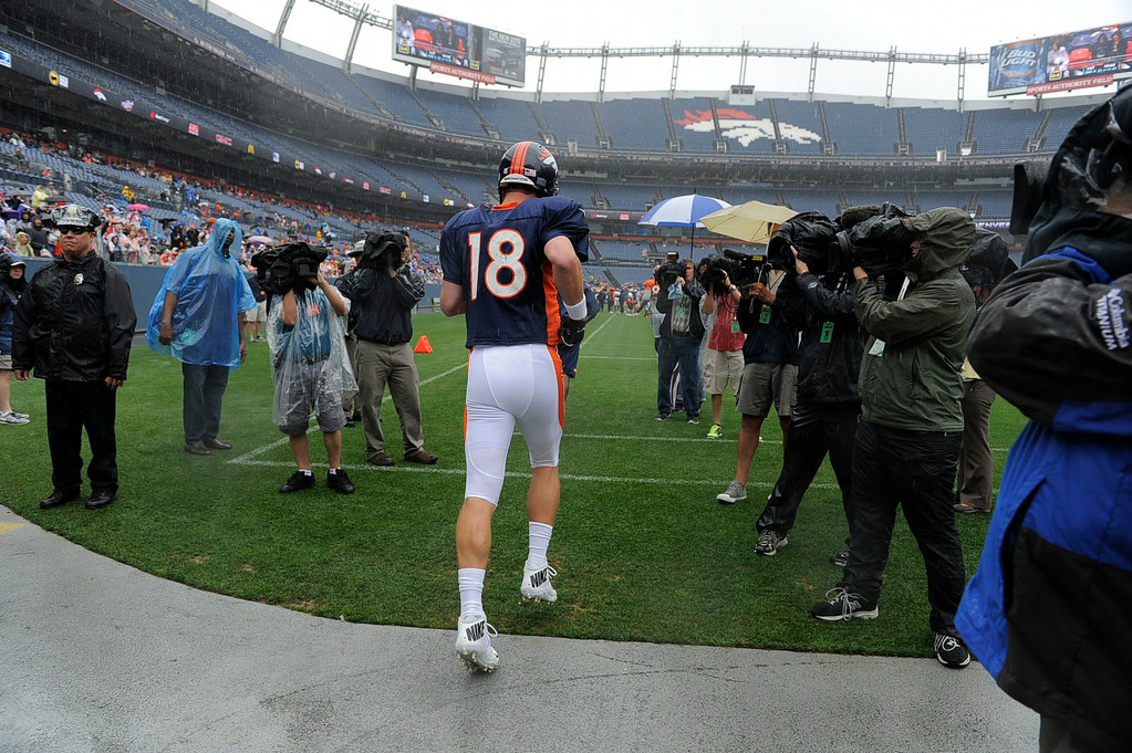 . Denver Broncos quarterback Peyton Manning (18) takes to the field during a day six of the  Denver Broncos 2014 training camp July 30, 2014 at Sports Authority Field at Mile High Stadium. The team practiced in the rain. (Photo by John Leyba/The Denver Post)