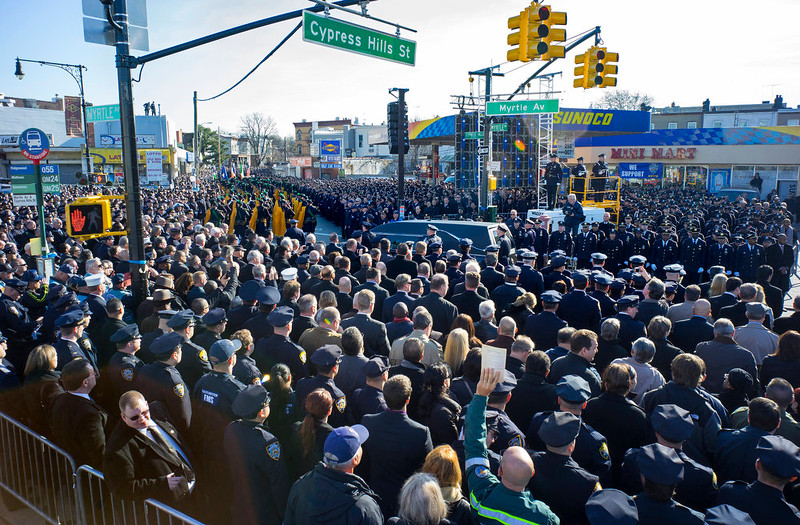 . Thousands of police officers stand at attention as a hearse carrying New York City police officer Rafael Ramos passes by after his funeral at Christ Tabernacle Church in the Glendale section of Queens, where he was a church member, Saturday, Dec. 27, 2014, in New York. Ramos and his partner, officer Wenjian Liu, were killed Dec. 20 as they sat in their patrol car on a Brooklyn street. The shooter, Ismaaiyl Brinsley, later killed himself.� (AP Photo/Craig Ruttle)