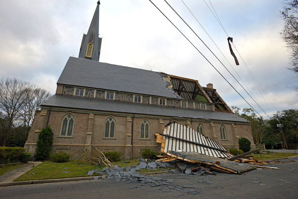Description of . A portion of Trinity Episcopal Church's roof lies on the ground beside it as residents clean up and assess the damage from a Christmas Day tornado Wednesday, Dec. 26, 2012  in Mobile, Ala. With only a handful of injuries and no deaths reported statewide from the storms, the head of the state's emergency response said it was difficult to fathom how the toll wasn't worse. (AP Photo/G.M. Andrews)