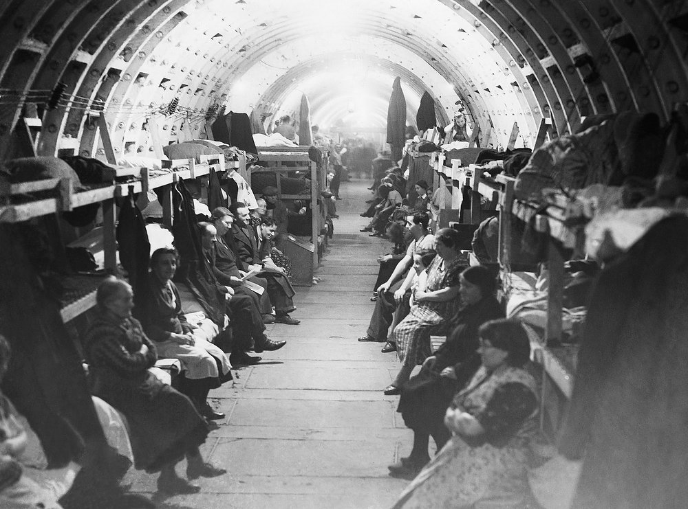 Description of . Shelter life is now fully established once more with the coming of the long dark on Oct. 18, 1941 in London's biggest air raid shelter, in the making of which part of a tube tunnel has been utilized. Communal life is here seen in many phases, for boredom has to be defeated as well as Hitler during the long winters underground. A general view of this mammoth London shelter, showing the many people who are already using it in case the blitzes start again-sitting on their bunks before settling down for the night. (AP Photo)